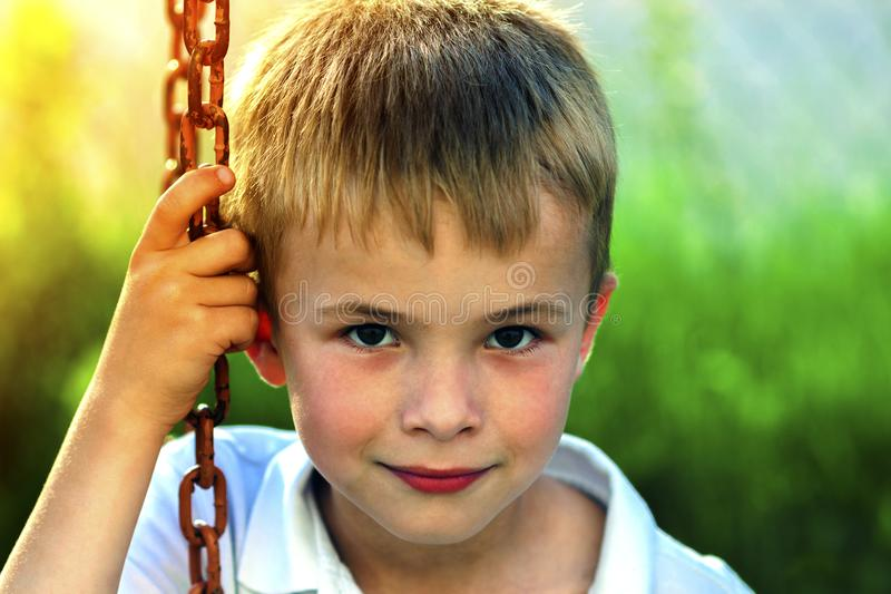 Portrait of a little smiling boy with golden blonde straw hair i. N sunny summer day on green blurred background stock photos