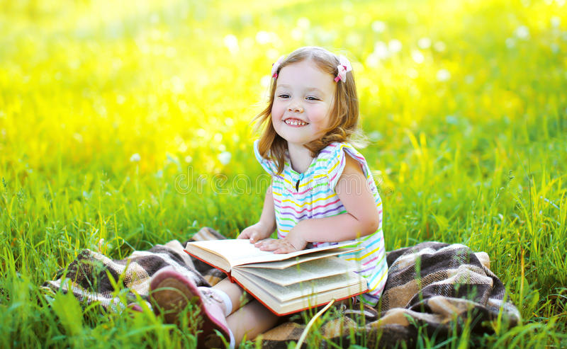 Portrait of little smiling girl child with book sitting. On the grass in sunny summer day stock photography