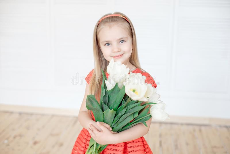Portrait of little smiling girl child in colorful dress. Portrait of little smiling girl child in red dress holding a bouquet of white tulips indoor royalty free stock photography