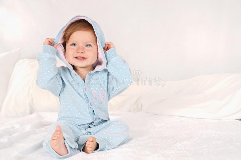 Portrait of a little smiling girl dressed in blue pajamas at home royalty free stock image