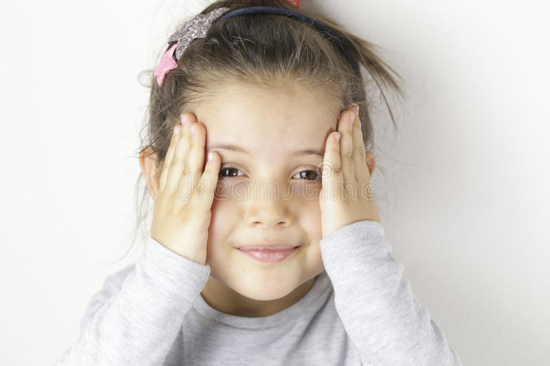 Portrait of little smiling impressed cheerful girl in checkered holding her hands near face. stock photo