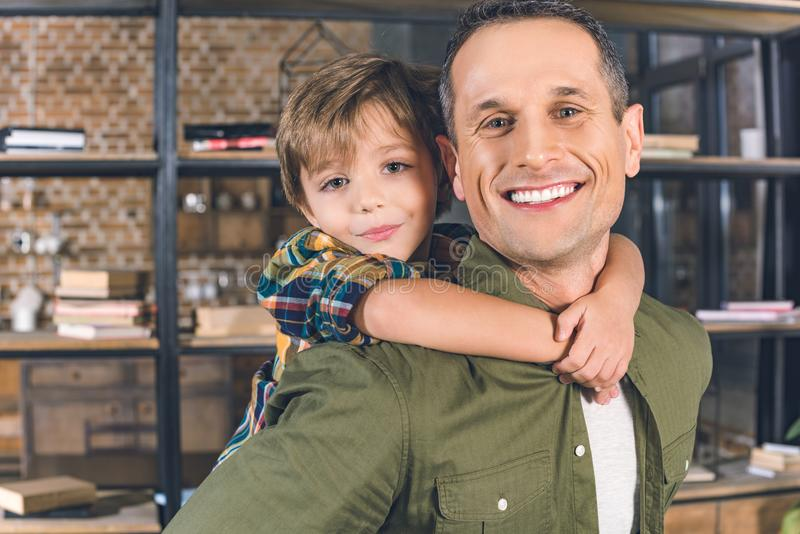 Portrait of little son hugging smiling father. At home stock photography