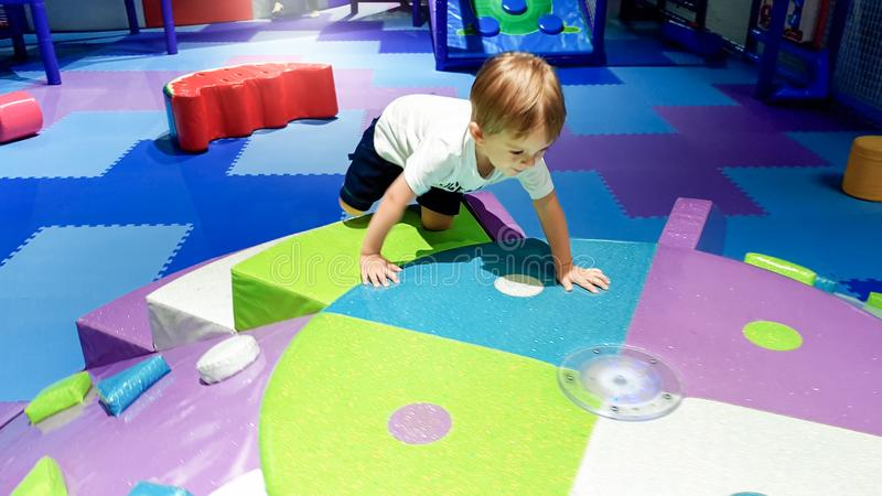 Portrait of little toddler boy crawling and playing on the colorful children palyground covered with soft mats in royalty free stock photo