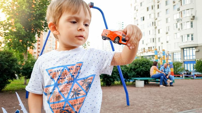 Portrait of little toddler boy playing with toy cars on the playground. Portrait of little toddler boy playing with toy cars on playground royalty free stock photos