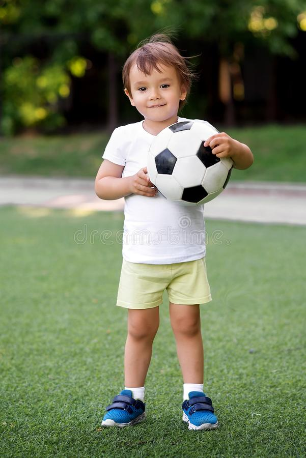 Portrait of little toddler child standing in green football field holding soccer ball. Smiling little football player at stadium royalty free stock photo