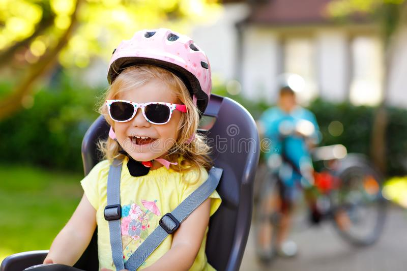 Portrait of little toddler girl with security helmet on the head sitting in bike seat of parents. Boy on bicycle on stock images