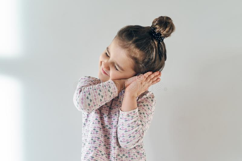 portrait of a little young girl on a white background with a sleepy and happy expression with folded hands to the ear stock photos