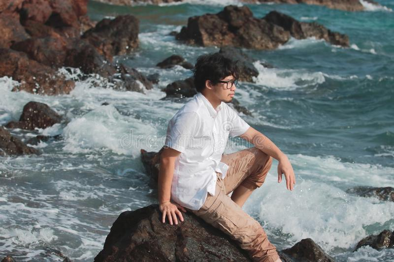 Portrait of lonely Asian man sitting on the rock of natural seashore. Vacations summer concept. stock images