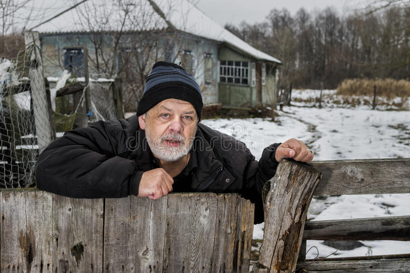 Portrait of lonely Ukrainian old man with tearful face standing at his fence near neglected house in rural Ukrainian village. Outdoor portrait of lonely royalty free stock photos