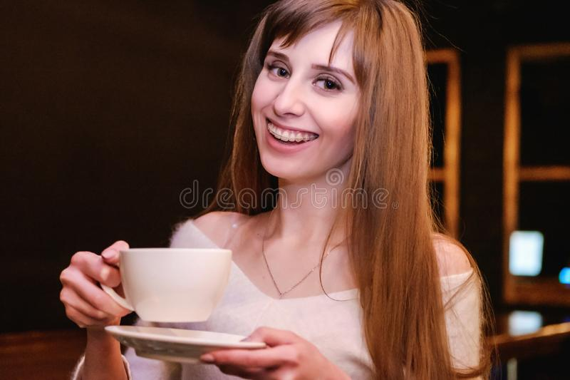 Portrait of a long-haired beautiful girl in a white sweater. A girl stands in a coffee shop at a wooden table and holds a cup of stock photos