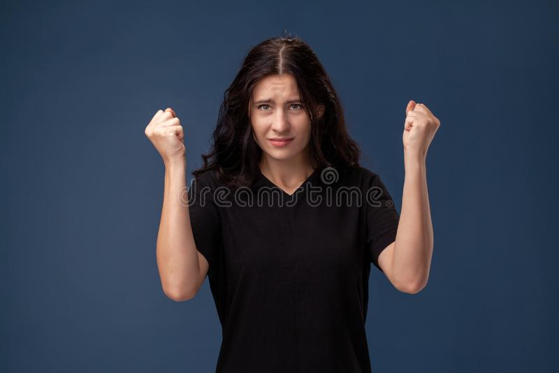 Portrait of a long-haired brunette woman in black t-shirt posing on a gray background and showing different emotions. royalty free stock image