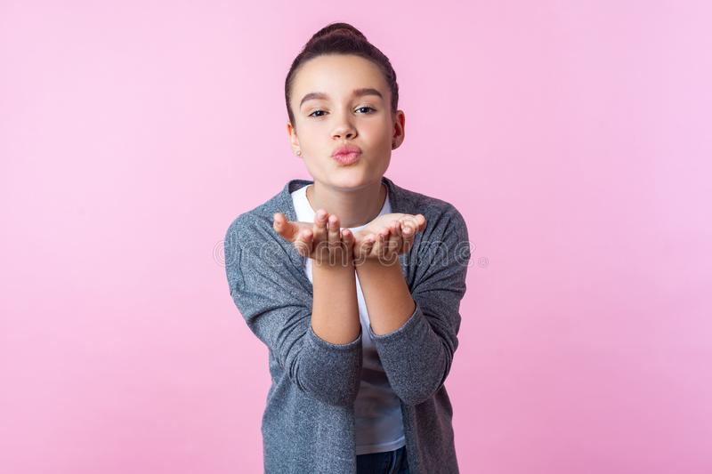 Portrait of lovely brunette teenage girl sending air kiss with pout lips, experiencing romantic feelings in adolescence. indoor stock photography