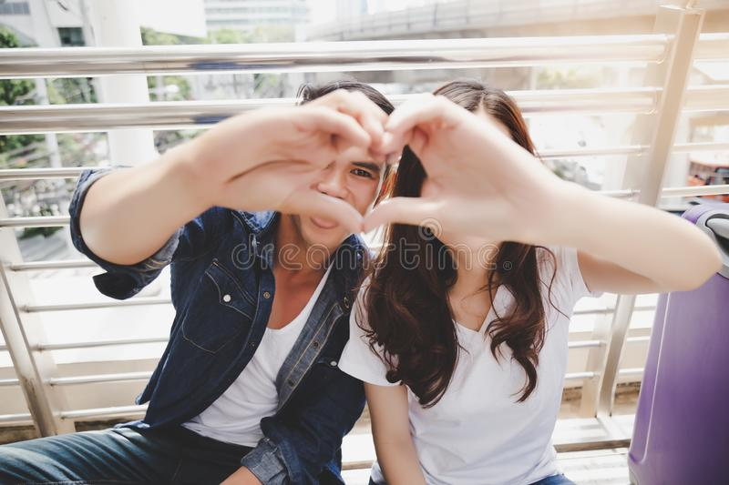 Portrait lovely couple. Handsome boyfriend and beautiful girlfriend is making symbol of love by using their hand and fingers for royalty free stock photo