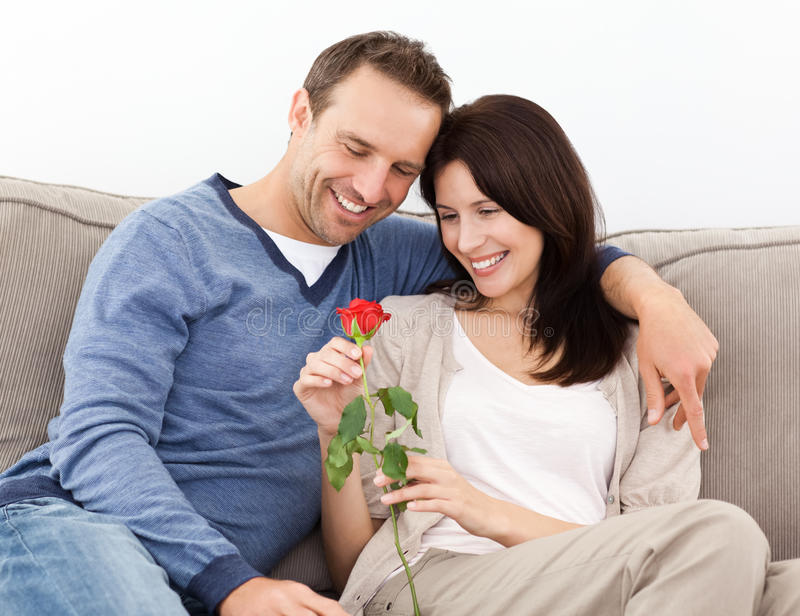 Portrait of a lovely couple looking at a red rose royalty free stock photography