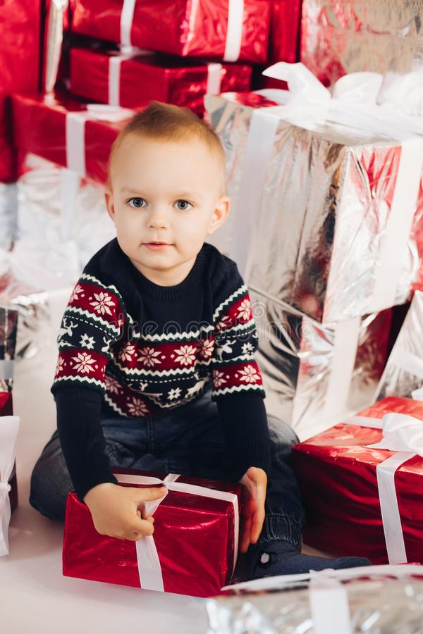 Cute boy in sweater with wrapped red Christmas present. royalty free stock photography