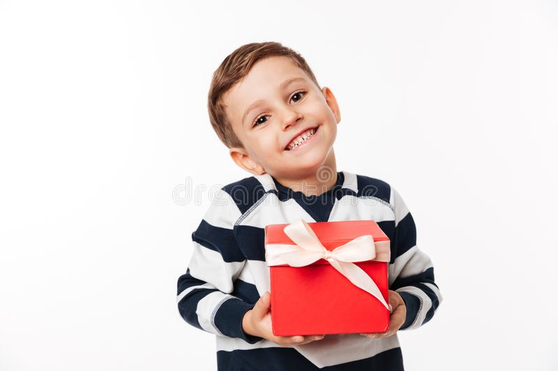 Portrait of a lovely cute little kid holding present box. And looking at camera isolated over white background royalty free stock photos
