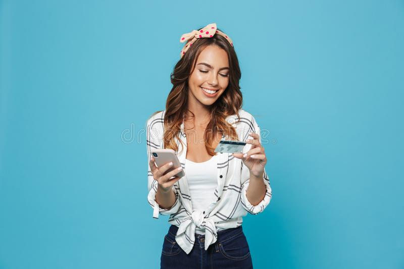 Portrait of lovely excited lady 20s wearing headband smiling while holding mobile phone and credit card, isolated over blue stock photography
