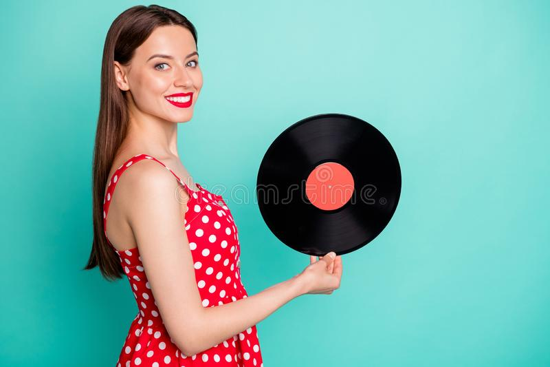 Portrait of lovely girl holding vinyl record disc smiling wearing dotted dresss skirt isolated over green teal turquoise. Portrait of lovely girl holding vinyl stock photo