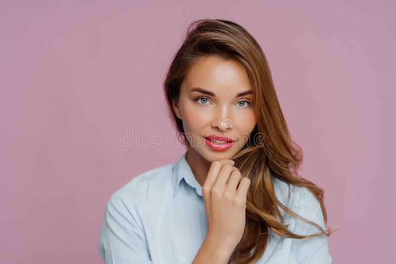 Portrait of lovely long haired woman touches chin, has blue eyes, looks confidently at camera, wears casual shirt, has makeup for. Looking beautiful, poses stock photography