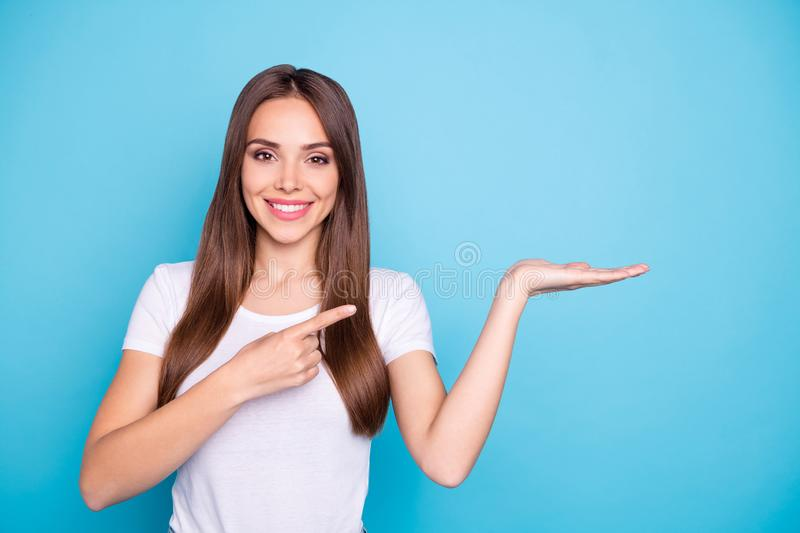 Portrait of lovely millennial holding hand pointing to ads with her index finger  over blue background stock photos