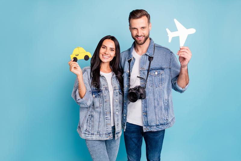 Portrait of lovely spouses holding paper card plane and taxi camera wearing denim jeans jackets  over blue royalty free stock image