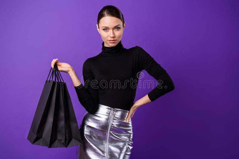 Portrait of lovely woman holding bags looking wearing black turtleneck silver skirt isolated over purple violet stock photography