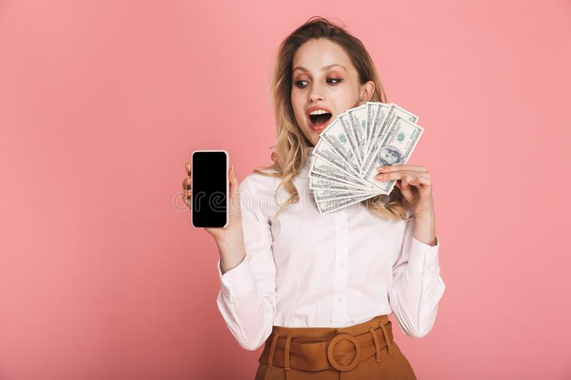 Portrait of lovely woman holding cell phone and money fan isolated over pink background stock image