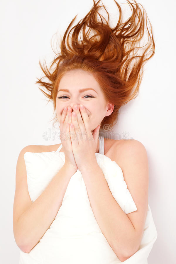 Portrait of lovely woman with pillow. Portrait of lovely redheaded woman with pillow on white stock image