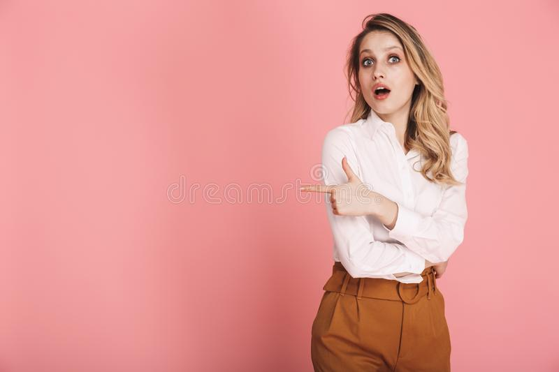 Portrait of lovely woman smiling and pointing finger at copyspace isolated over pink background stock photos