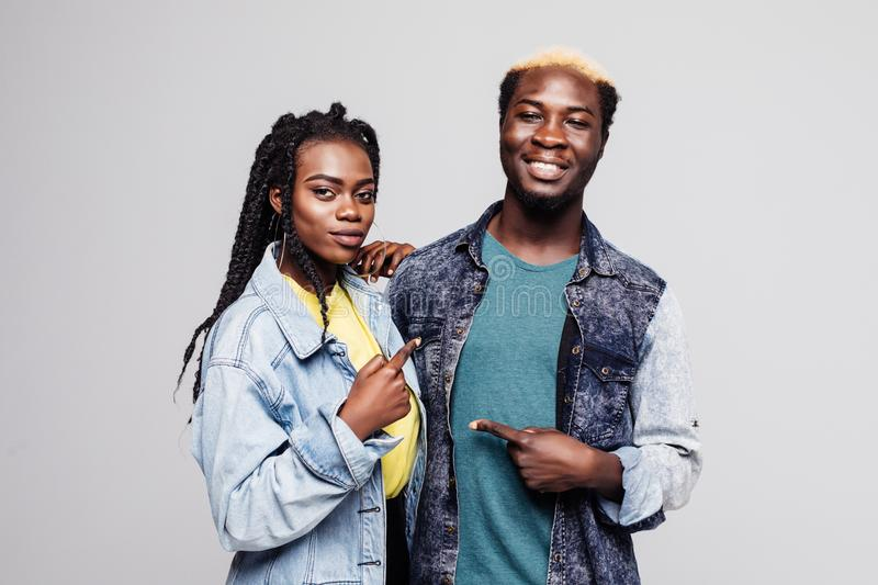 Portrait of a lovely young afro american couple pointing fingers at each other isolated over white background stock image