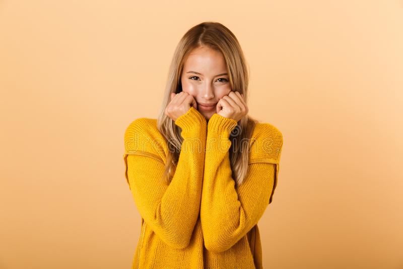 Portrait of a lovely young woman dressed in sweater. Standing isolated over yellow background, holding hands at her face stock photos