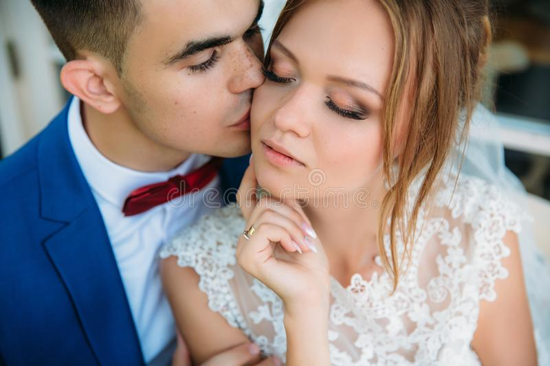 Portrait of lovers. The man gently kisses the woman. The bride fully enjoys the moment, the man admires her beautiful stock image