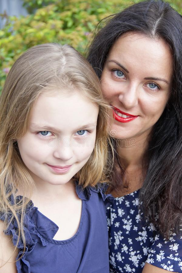 Loving brunette mother and blond daughter. Portrait of loving brunette mother and blond daughter royalty free stock photos
