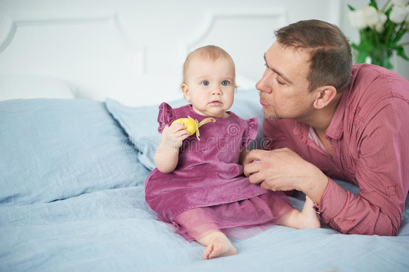 Portrait of loving father playing with his 10 months old baby in bedroom stock photos
