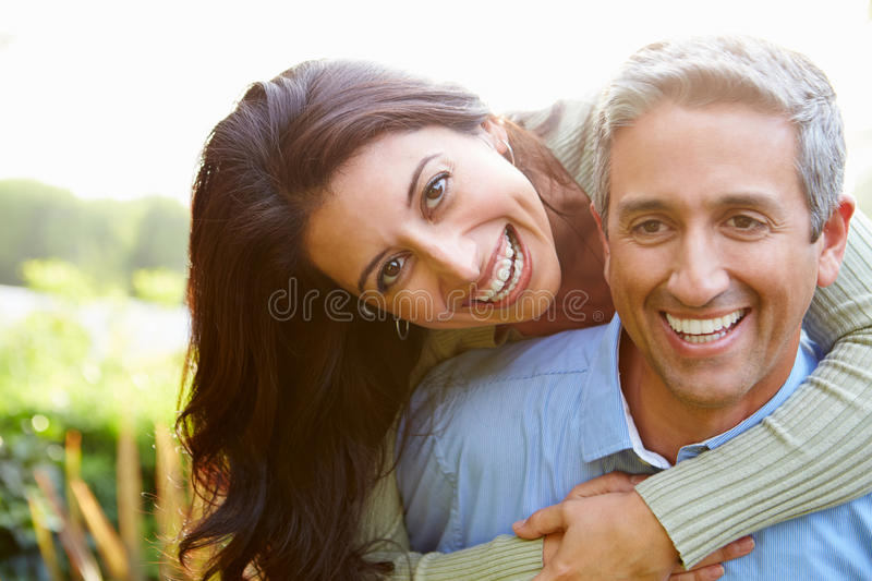 Portrait Of Loving Hispanic Couple In Countryside. Smiling To Camera stock images