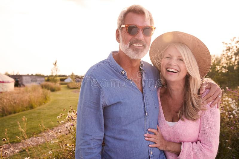 Portrait Of Loving Mature Couple In Countryside Hugging Against Flaring Sun royalty free stock image