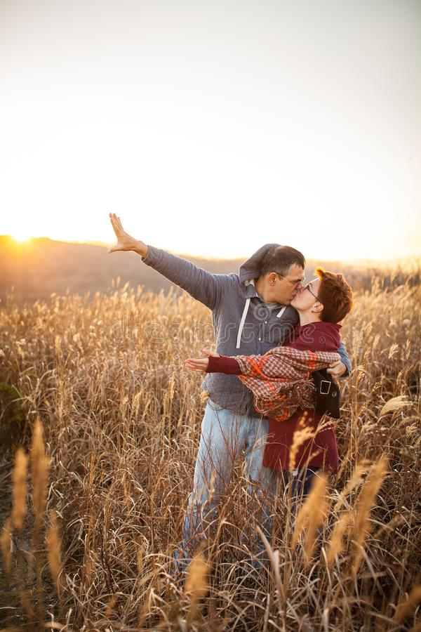 Portrait of loving middle-aged couple in warm clothes hugging in the autumn park at sunset in selective focus stock photo