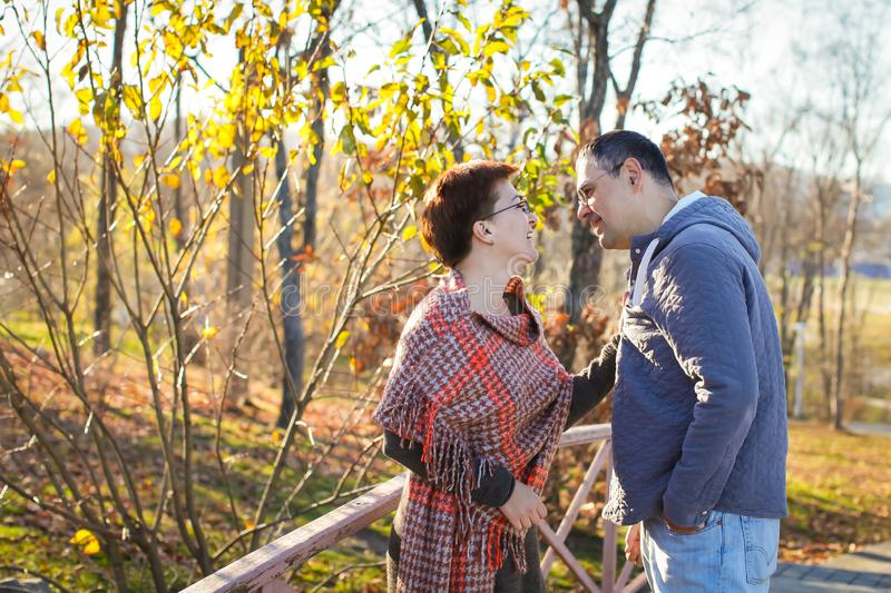 Portrait of loving middle-aged couple in warm clothes hugging in the autumn park at sunset in selective focus royalty free stock image