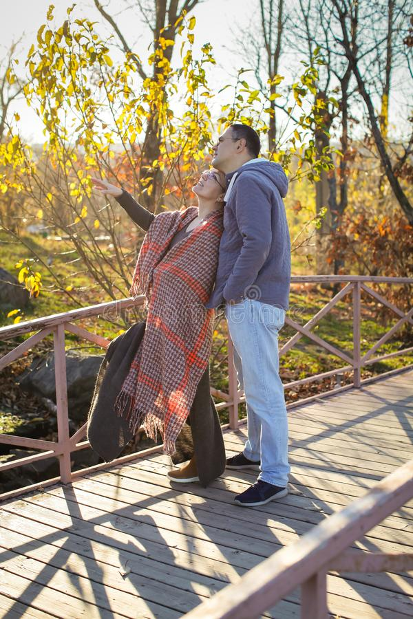 Portrait of loving middle-aged couple in warm clothes hugging in the autumn park at sunset in selective focus royalty free stock photos