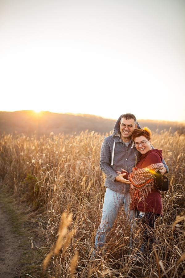 Portrait of loving middle-aged couple in warm clothes hugging in the autumn park at sunset in selective focus stock photography