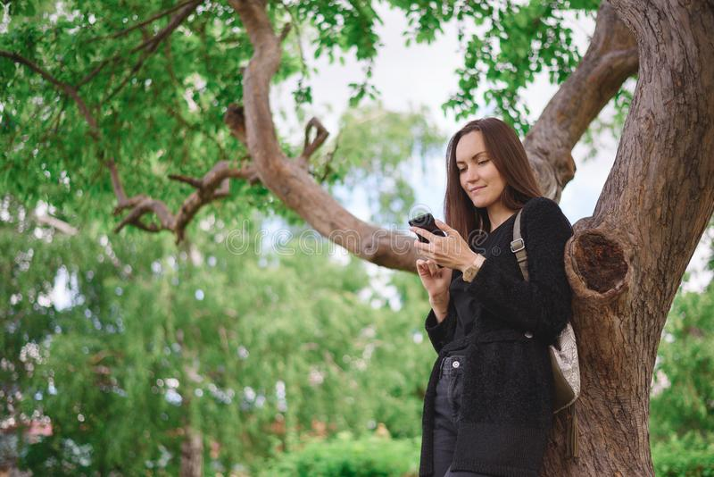 Portrait from the lower angle of a young woman in a black jacket with a smartphone in her hands on the background of a large branc stock photo