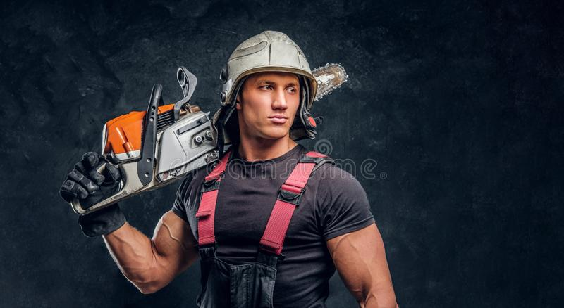 Portrait of a lumberjack wearing protective clothes posing with a chainsaw. Lumberjack wearing protective clothes posing with a chainsaw royalty free stock photos