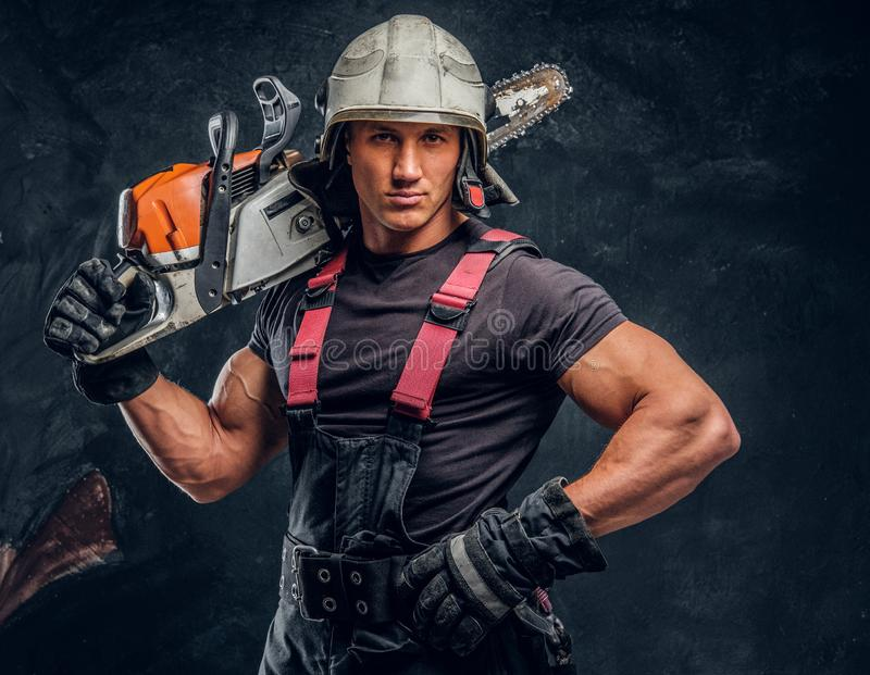 Portrait of a lumberjack wearing protective clothes posing with a chainsaw. Brutal logger wearing protective clothes and helmet posing with a chainsaw on his royalty free stock image