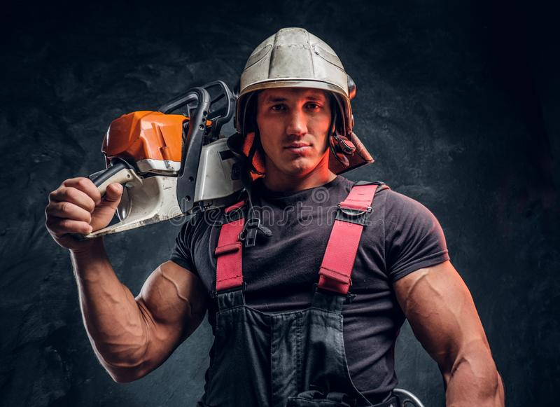 Portrait of a lumberjack wearing protective clothes posing with a chainsaw. Brutal logger wearing protective clothes and helmet posing with a chainsaw on his stock images