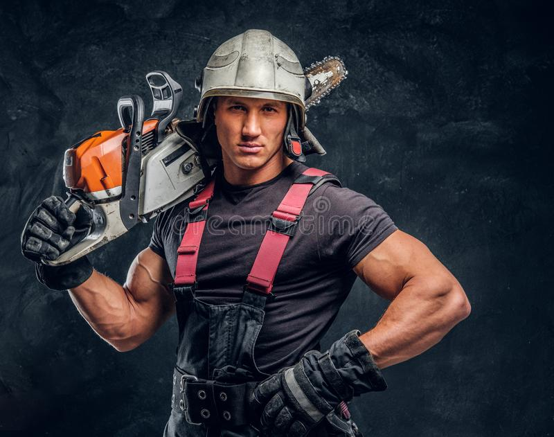 Portrait of a lumberjack wearing protective clothes posing with a chainsaw. Brutal logger wearing protective clothes and helmet posing with a chainsaw on his royalty free stock photos