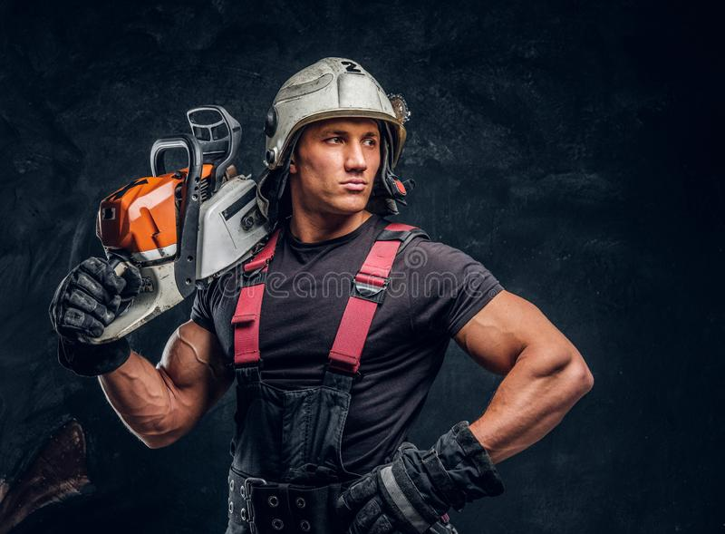Portrait of a lumberjack wearing protective clothes posing with a chainsaw. Young lumberjack wearing protective clothes posing with a chainsaw and looks sideways stock photography