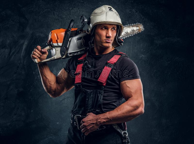 Portrait of a lumberjack wearing protective clothes posing with a chainsaw. Young lumberjack wearing protective clothes posing with a chainsaw and looks eways in royalty free stock photography