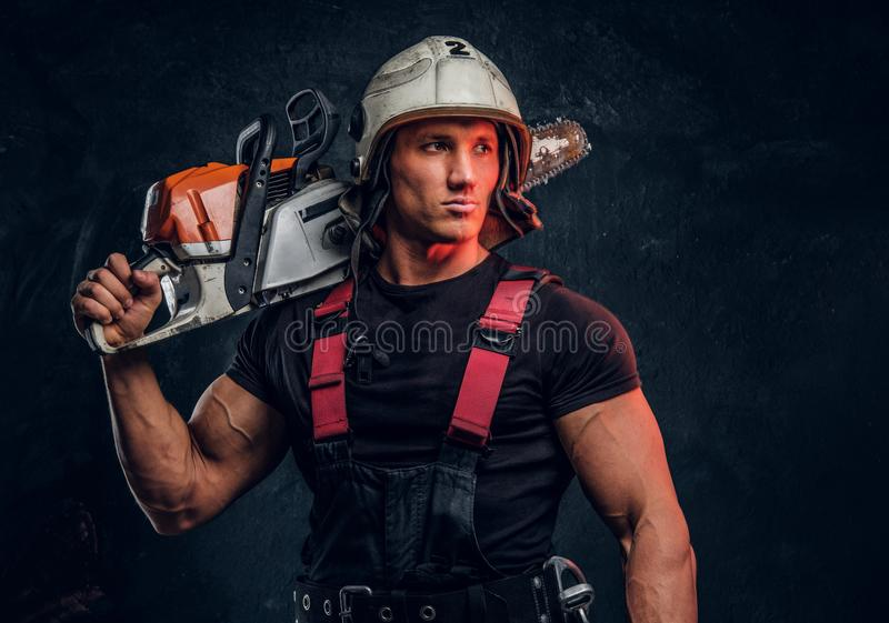 Portrait of a lumberjack wearing protective clothes posing with a chainsaw. Young lumberjack wearing protective clothes posing with a chainsaw and looks eways in royalty free stock image