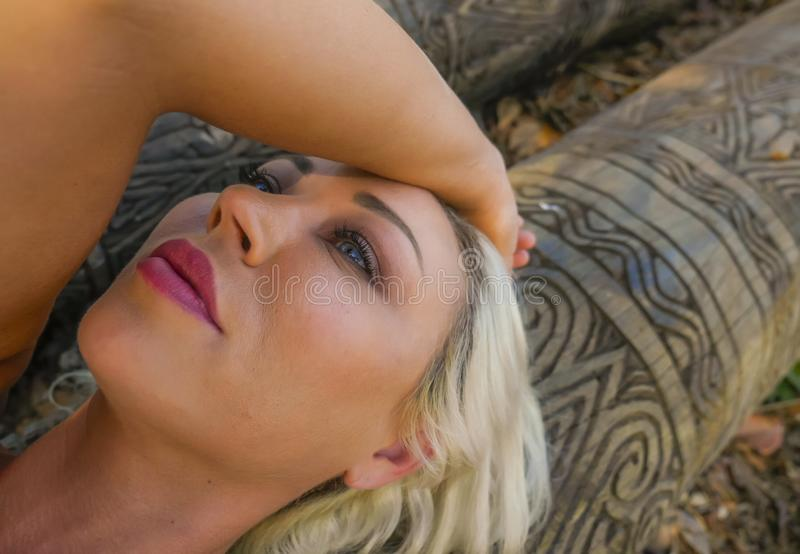 Portrait mélancolique d'extérieur du jeune mensonge blond attrayant et beau de femme détendu sur le tronc à la forêt ou au parc d photographie stock libre de droits