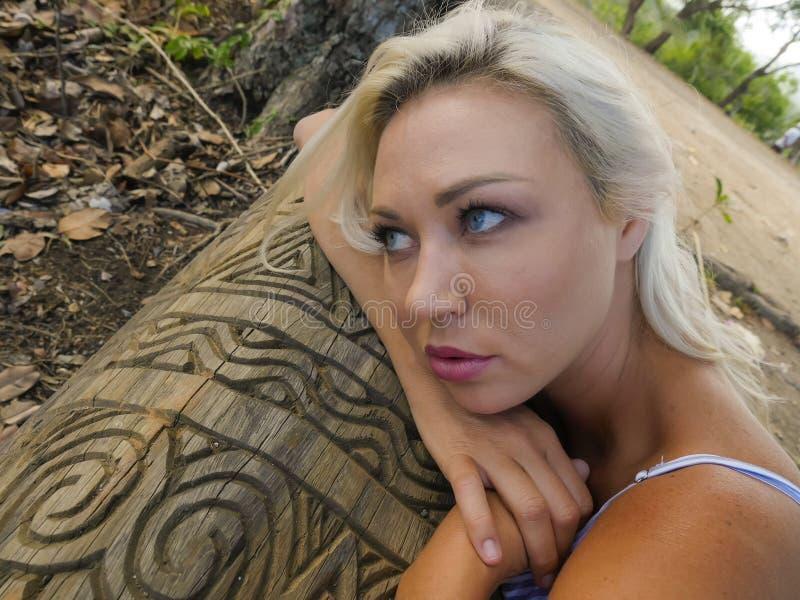 Portrait mélancolique de la jeune femme blonde attirante et belle se penchant son visage détendu sur le tronc à la forêt ou au pa photographie stock